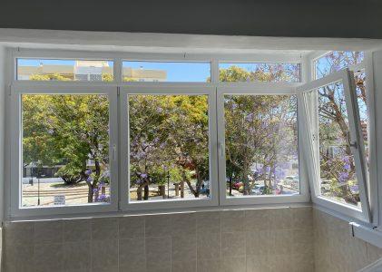 Cerramiento de balcón con ventanas oscilobatientes de PVC